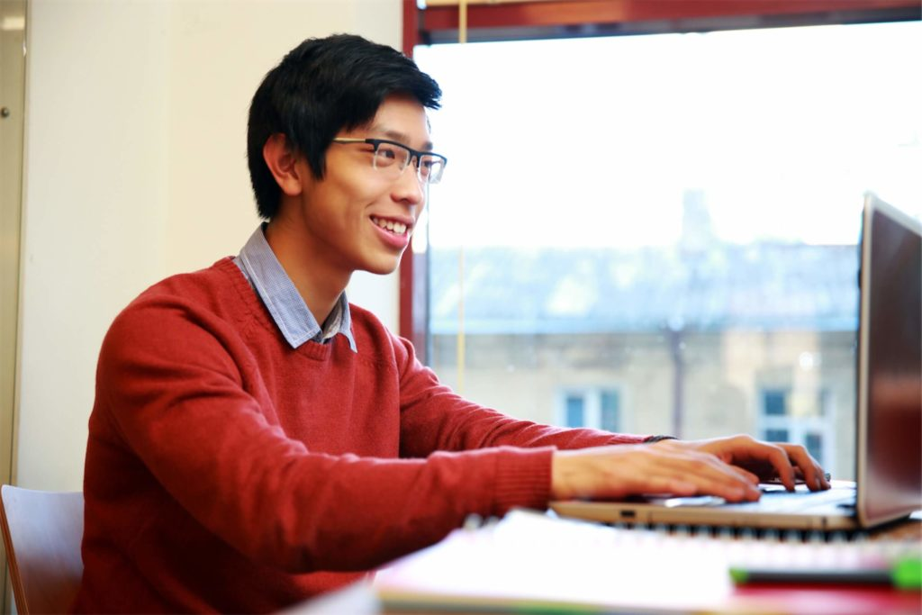 Smiling man in glasses working on laptop