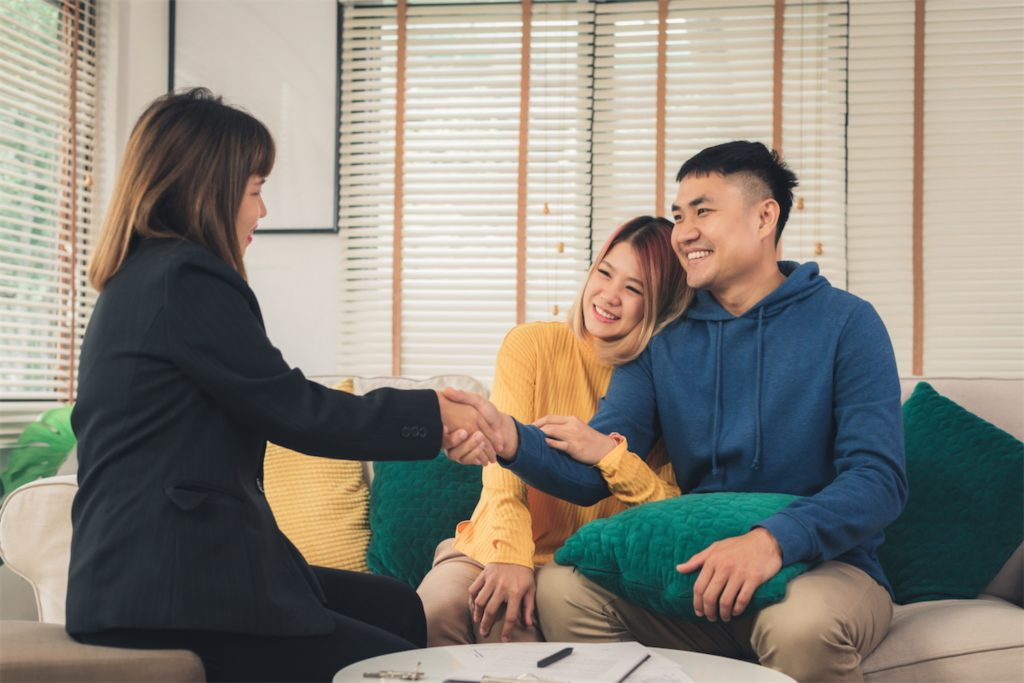 Couple smiling happily and shaking hands with licensed money lender in singapore