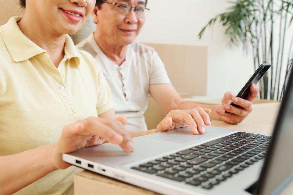 Senior couple working on laptops