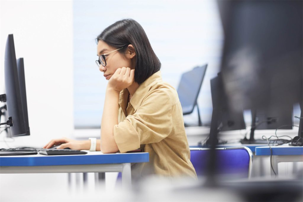 a woman using a desktop computer during a class that's paid with a personal loan in Singapore