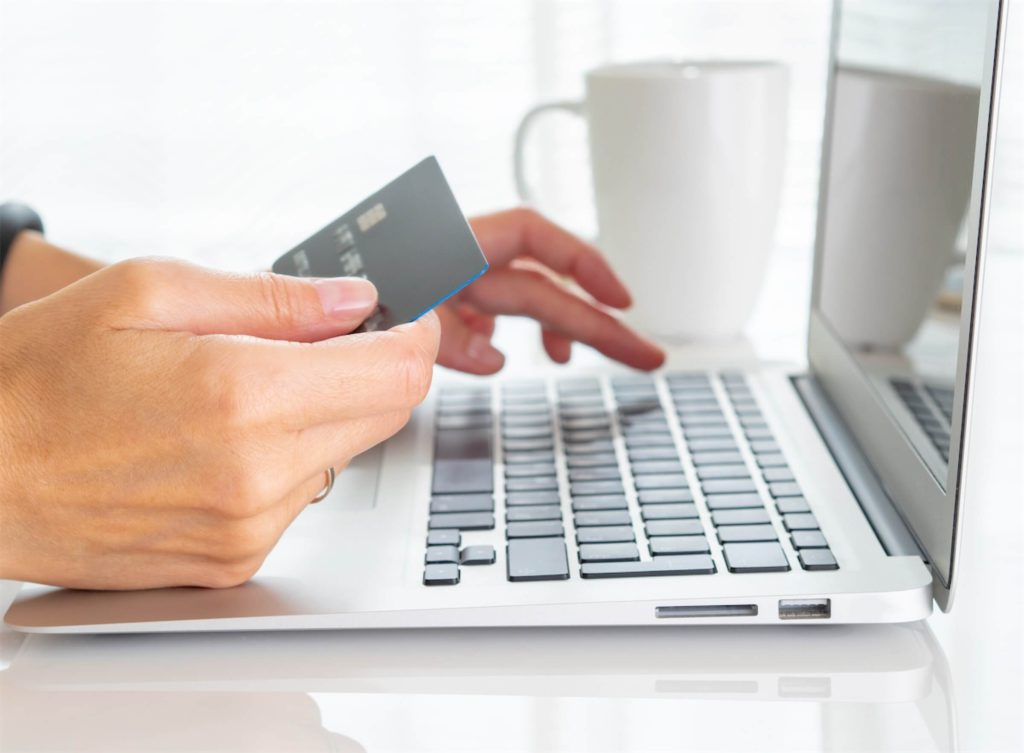 An individual entering credit card details on a laptop to apply for balance transfer, a type of personal loan in Singapore