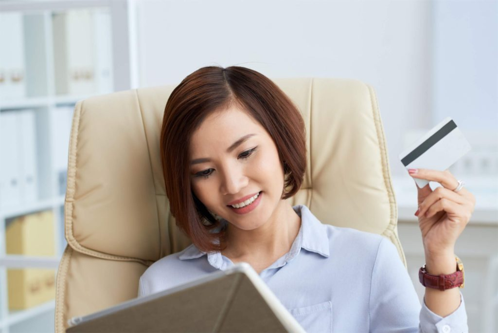 Woman holding a credit card and applying to increase the credit limit