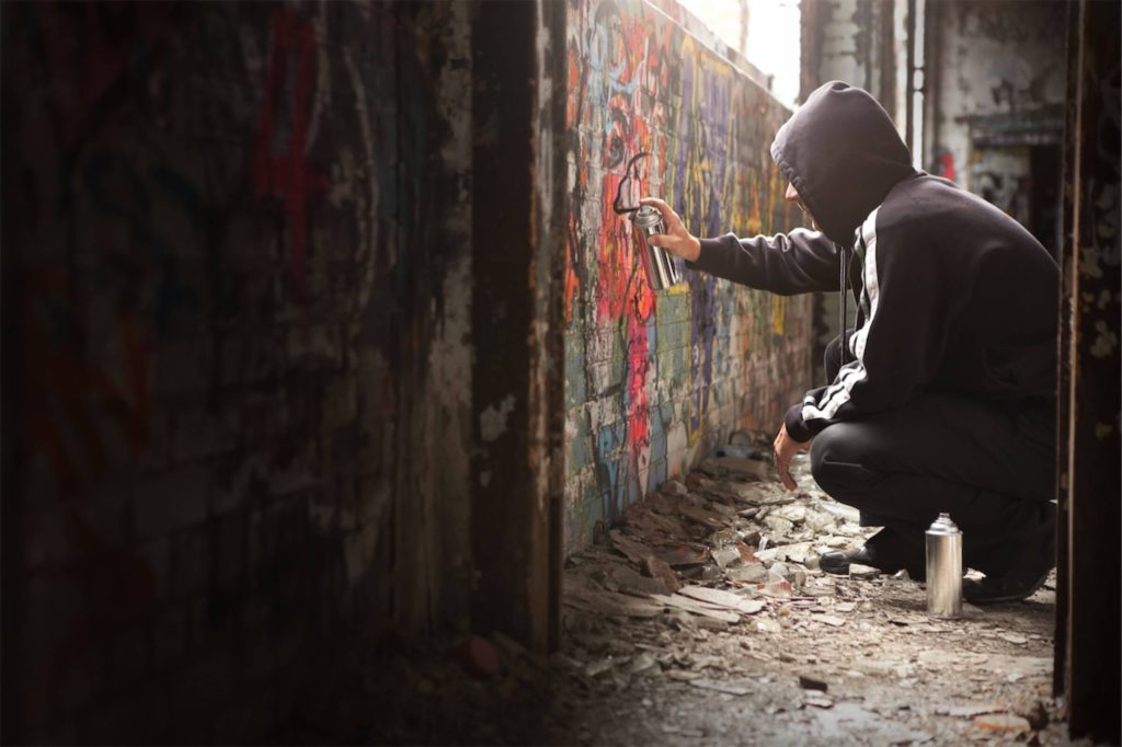 A loan shark vandalising property with paint