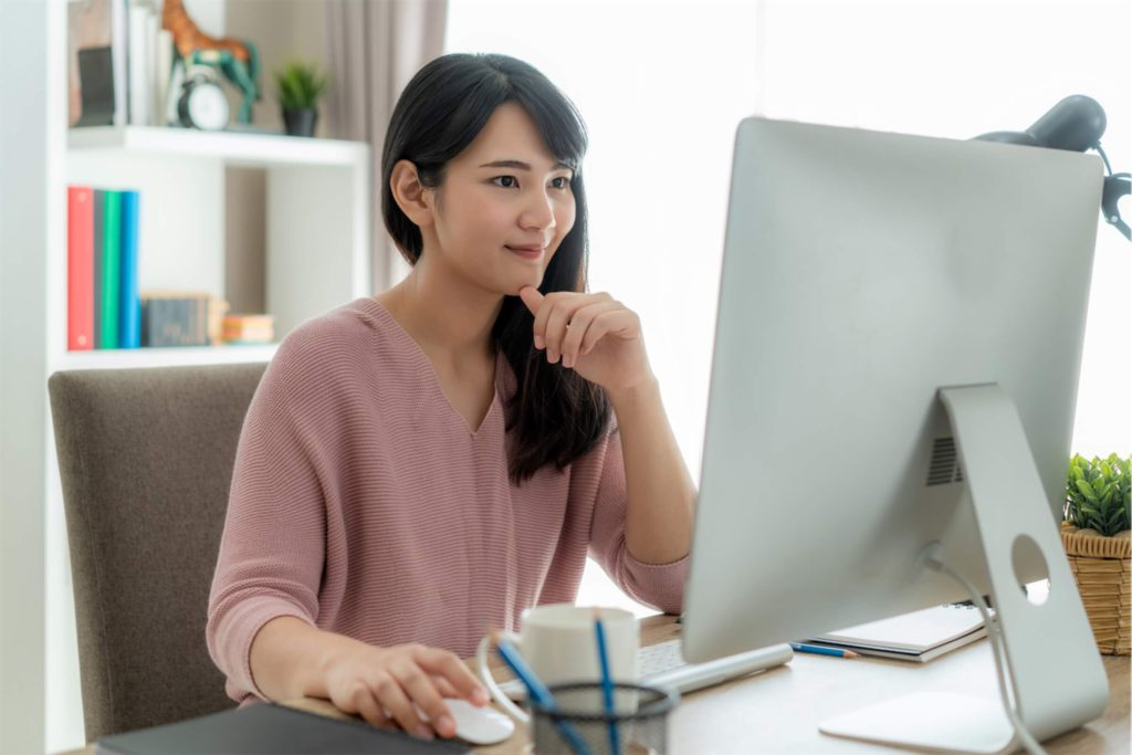 A woman looking at her desktop monitor and taking a short-term course in Singapore, paid using a personal loan
