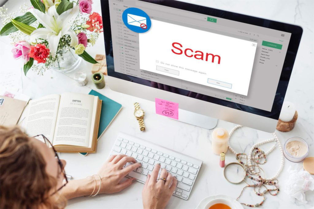 Woman on computer with a scam popup
