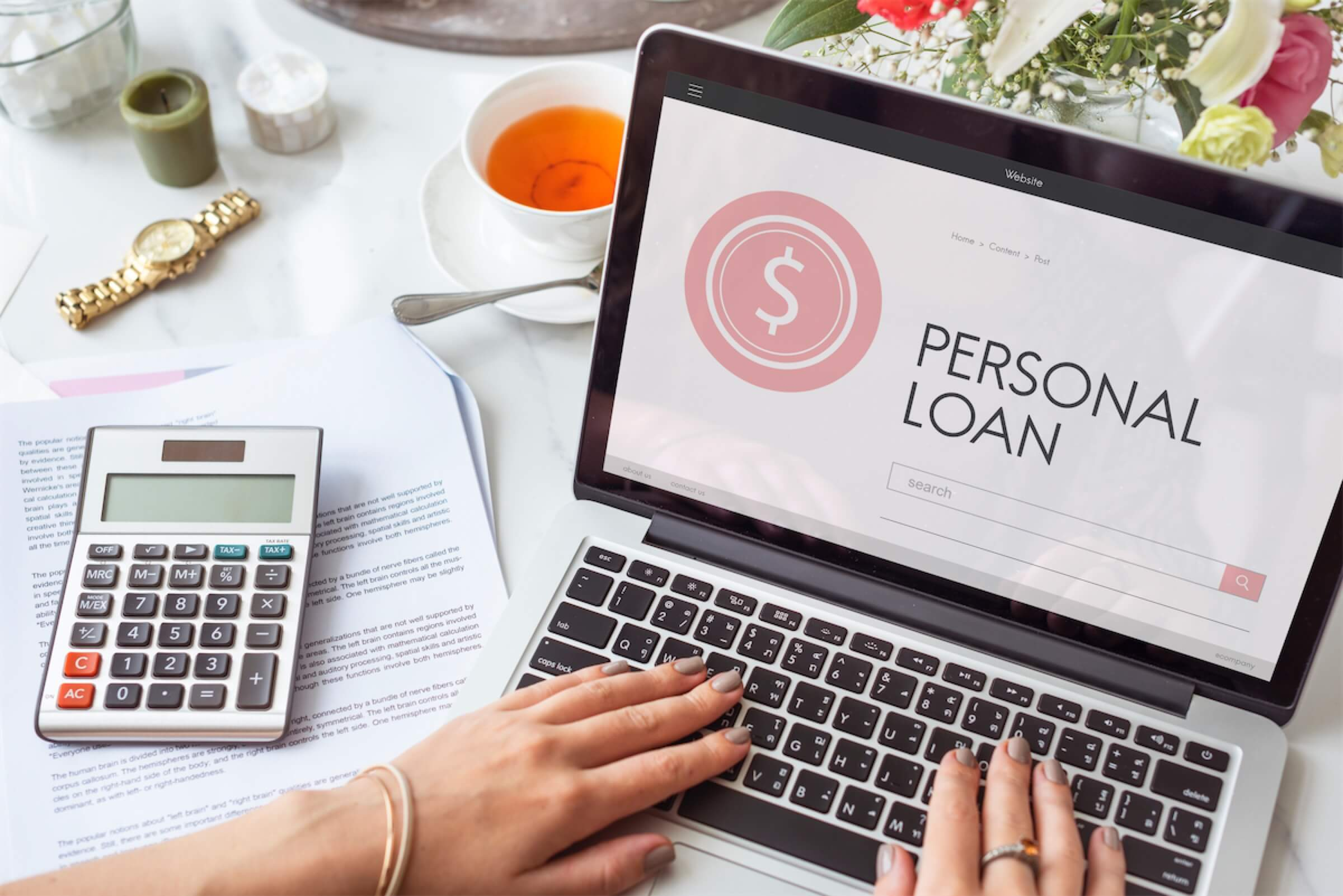 A woman with a calculator and laptop searching for the best personal loan in Singapore