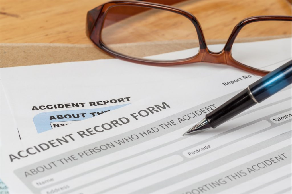 An accident record form, with a pen and a pair of glasses on top of it