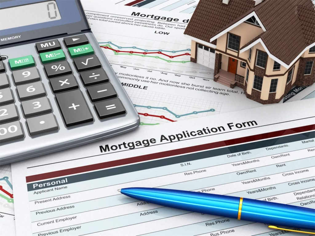 A mortgage application form, with a calculator and a pen on top of it